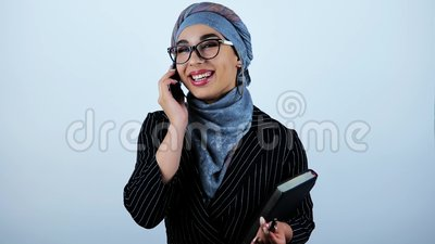 Giovani bei occhiali d'uso arabi della donna di affari che tengono pianificatore che ha riuscita conversazione sullo smartphone stock footage