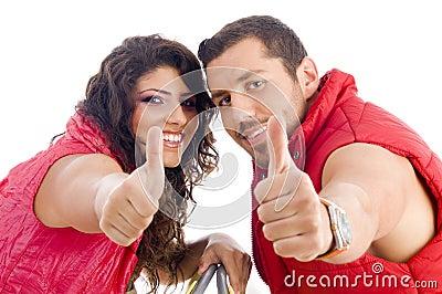 Giovani coppie allegre che mostrano i pollici in su