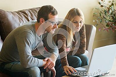 Giovani coppie che esaminano computer portatile