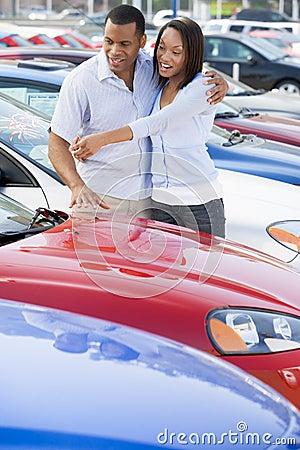 Giovani coppie che esaminano le nuove automobili