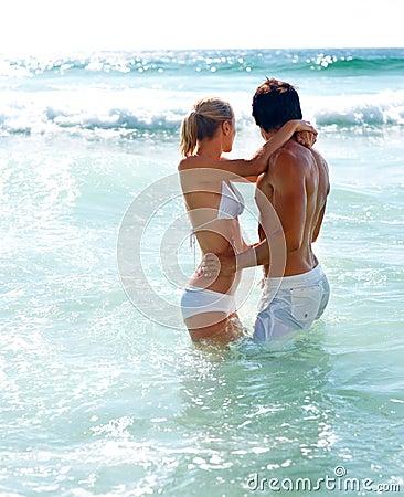 Giovani coppie che godono al mare