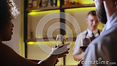 Giovani coppie che tostano il vetro di vino nella barra di lusso datare Pantaloni a vita bassa e donna di colore sulla cena roman archivi video