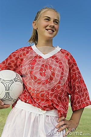 Girl (13-17) in soccer kit holding ball