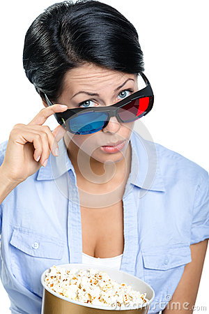 Girl in 3D glasses watching film with bowl of popcorn