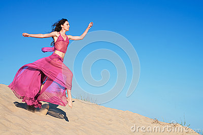 Girl in airy crimson dress running on sand dunes