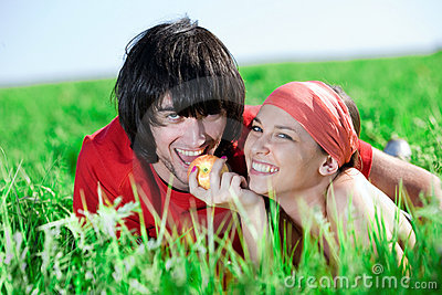 Girl with apple and boy on grass