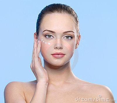 Girl applying cosmetic cream around eyes