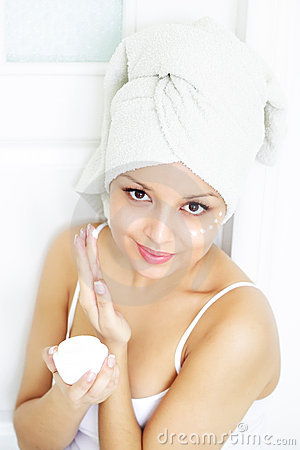 Girl applying cream on skin