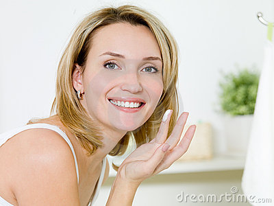 Girl applying moisturizer  cream on face