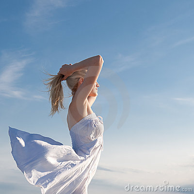Girl with arms raised on background of sea