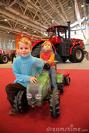 Girl astride small tractor, the boy sits next