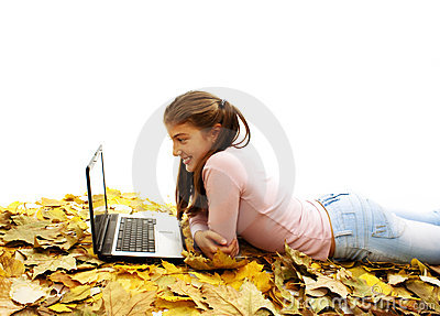 Girl in autumn leaves with laptop
