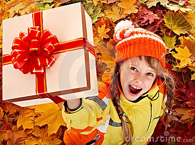 Girl in autumn orange  hat on leaf and gift box.