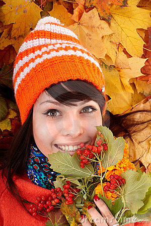 Girl in autumn orange hat on leaf group.