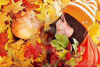 Girl in autumn orange leaves with pumpkin.