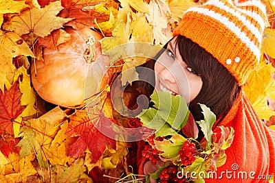 Girl in autumn orange leaves with pumpkin.