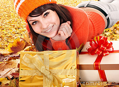 Girl in autumn outdoor holding gift box.