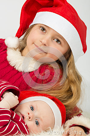 The girl with baby boy lie in the hats of Santa Claus