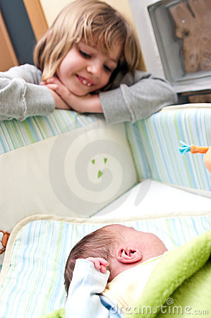 Girl and baby in crib