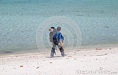 Girl backpacker walking on a beach