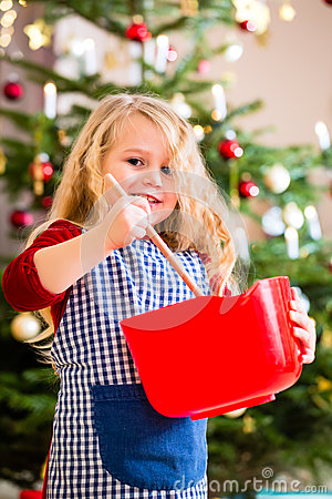 Free Girl Baking Cookies In Front Of Christmas Tree Stock Photo - 46179010