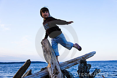 Girl Balancing on Driftwood at the Beach