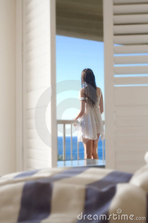 Girl on balcony looking at sea