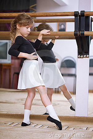 Girl at ballet barre. Ballet pas