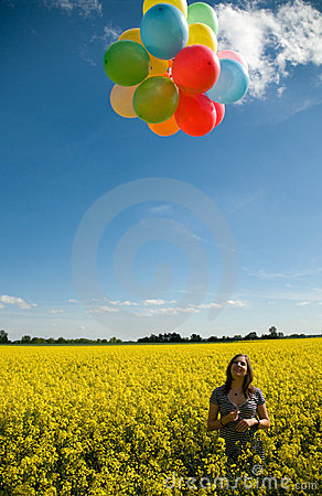 Girl with balloons on canola field.