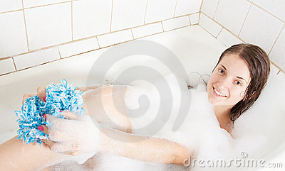 Girl in a bath with shower puff