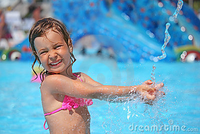 Girl bathes in pool under water splashes