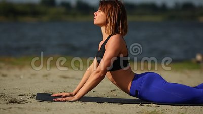 girl on the beach does exercise cobra pose from yoga