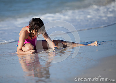 Girl on beach playing in sand