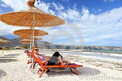 Girl on the beach under a parasol