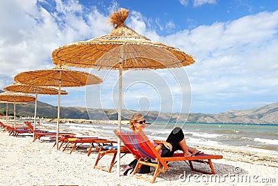 Girl on the beach under straw