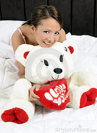 Girl in bed with a teddy bear