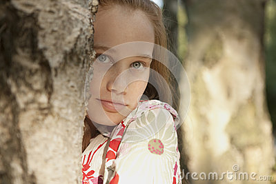 Girl behind Tree in Forest