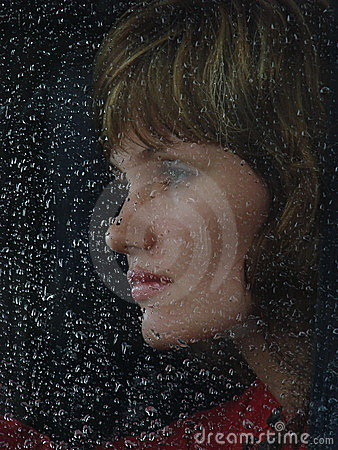 Girl behind waterdropped glass