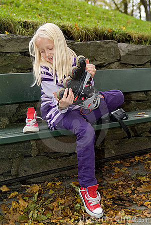 Girl on a bench taking of her rollerblades