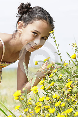 Girl Bending Down To Smell Flower In Field