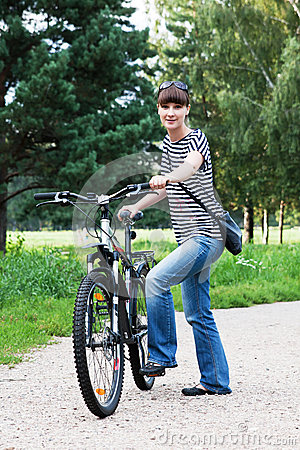 A girl with a bicycle in the park