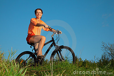 The girl on a bicycle in the summer evening