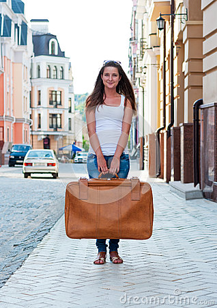 Girl with a big suitcase in the street.