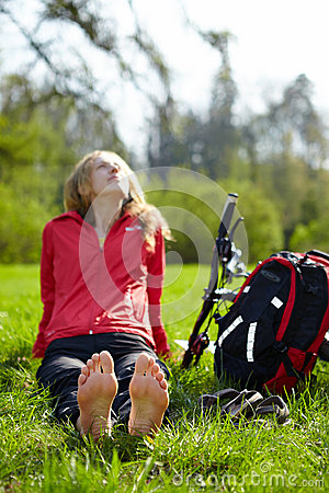 Free Girl Biker Barefoot Enjoying Relaxation Sitting In Fresh Green Grass Royalty Free Stock Photography - 31040247
