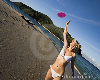 Girl in bikini catching a frisbee - tropical beach