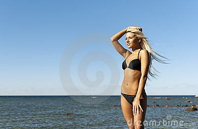 Girl in bikini posing near the sea