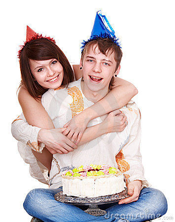 Girl in birthday hat kiss man with cake.