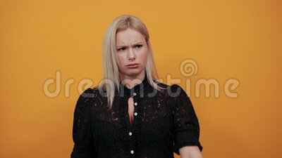 Girl in black dress angry woman shows protest turned her thumb down. Young blonde girl in black dress on yellow background angry woman shows protest turned her stock video footage