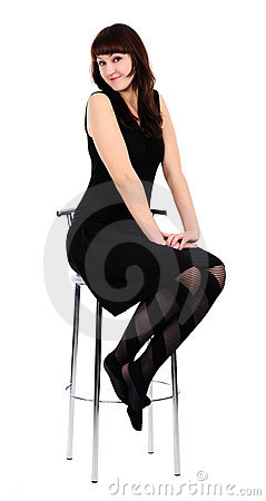 Girl in black dress sitting on a high chair