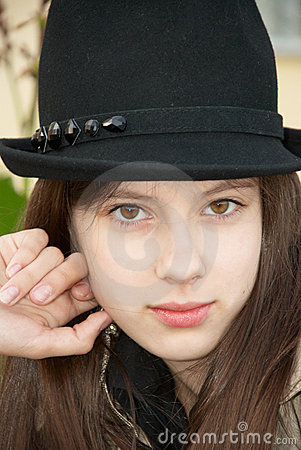 Girl in a black hat. Close-up